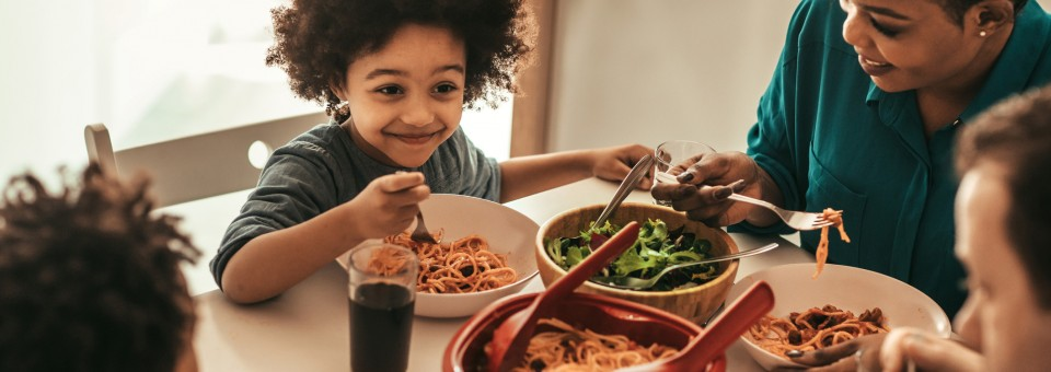 Young Boy Eating Dinner with Family